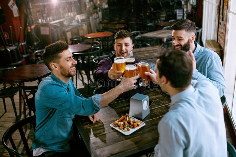 Män som dricker öl i bar arkivfoto