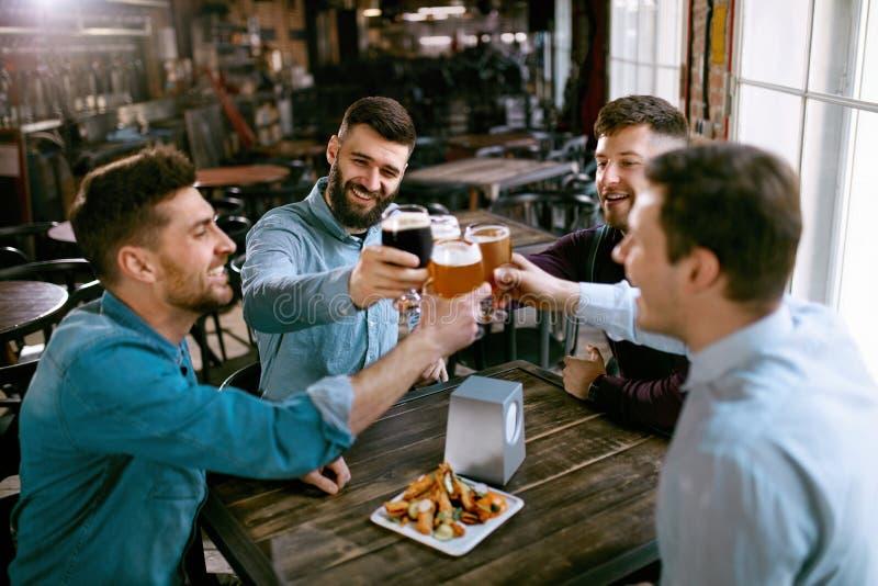 Män som dricker öl i bar arkivbild