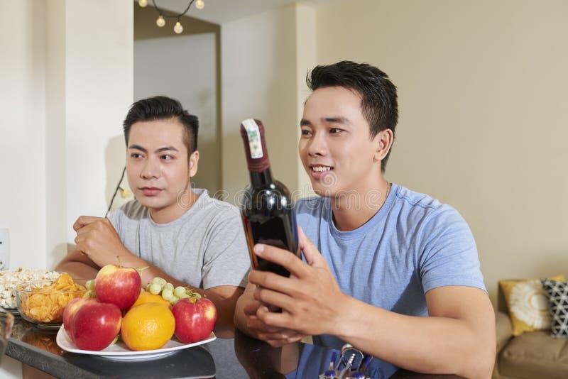 Män som dricker det hemmastadda partiet för vin arkivfoto