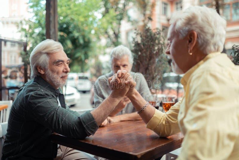 Män som försöker arm-brottning, medan sitta utanför bar arkivbilder