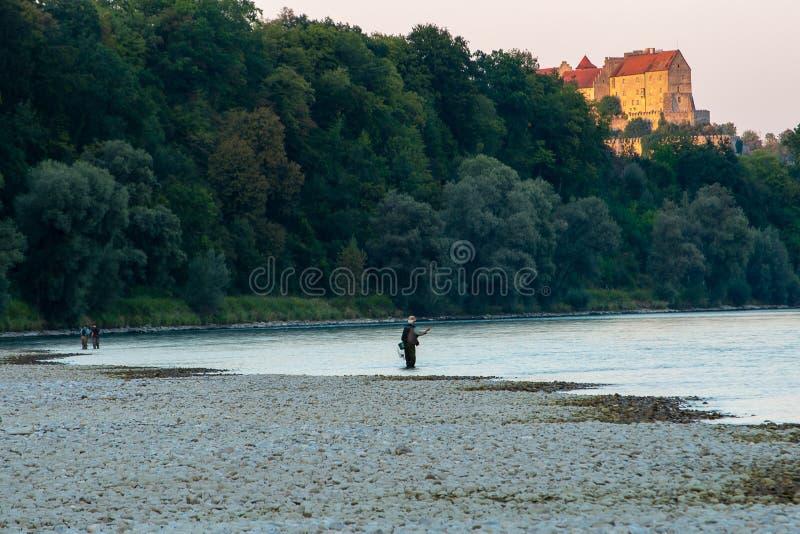 Män som gör klipskt fiske på solnedgången royaltyfri fotografi