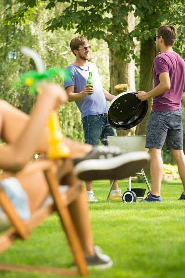 Män som grillar maten royaltyfri fotografi
