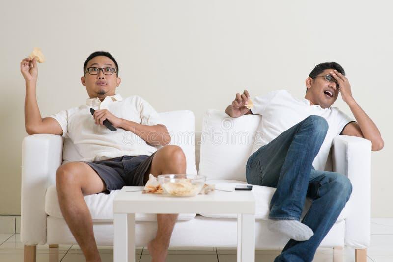 Män som håller ögonen på sporten att spela på tv hemma royaltyfri foto