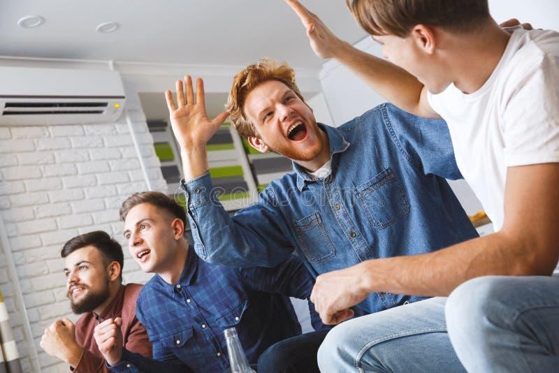 Män som håller ögonen på sporten på tv som ger tillsammans hemma lyckliga fem arkivfoto