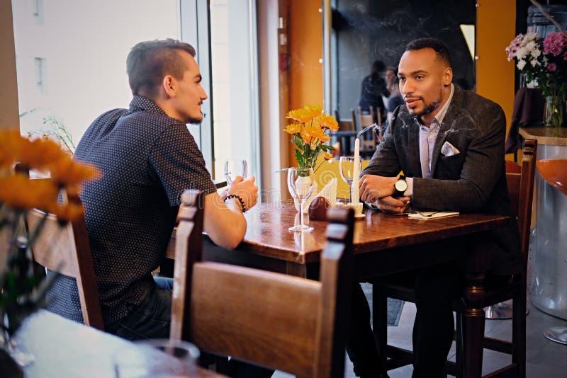 Män som har ett affärsmöte i en restaurang fotografering för bildbyråer