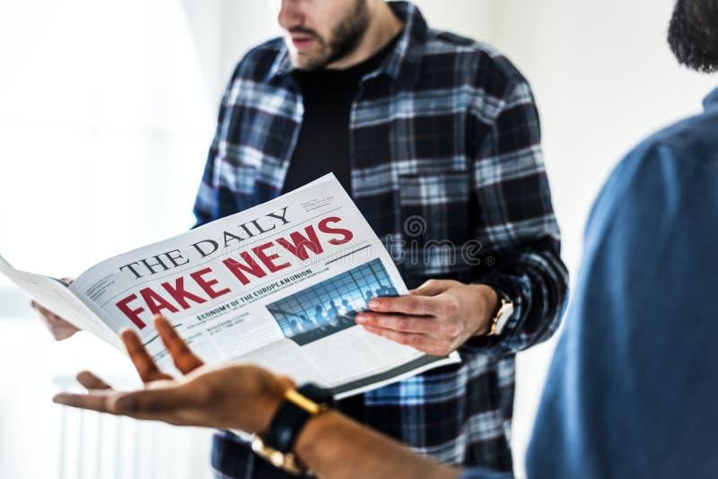 Män som läser den isolerade tidningen på vit bakgrund fotografering för bildbyråer
