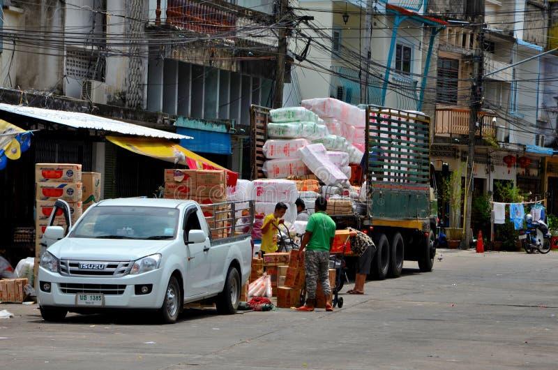 Män som lastar av gods på en spårvagn på basaren Pattani Thailand för vägsidomarknad royaltyfri foto