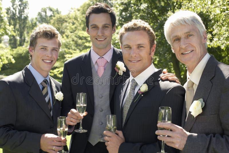 Män som rymmer Champagne Flutes At Wedding royaltyfri foto
