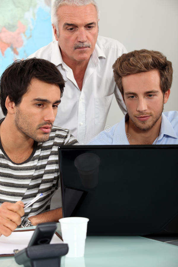 Män som sitter runt om bärbara datorn royaltyfri bild