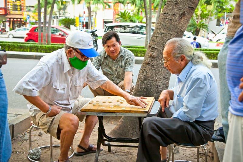 Män som spelar den traditionella brädeleken i Saigon, Vietnam royaltyfria foton
