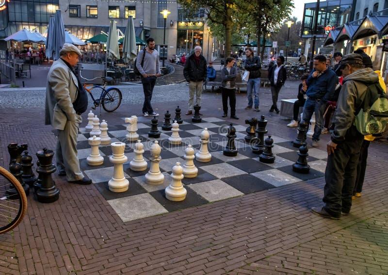 Män som spelar en lek av gataschack, Amsterdam, Nederländerna royaltyfri bild