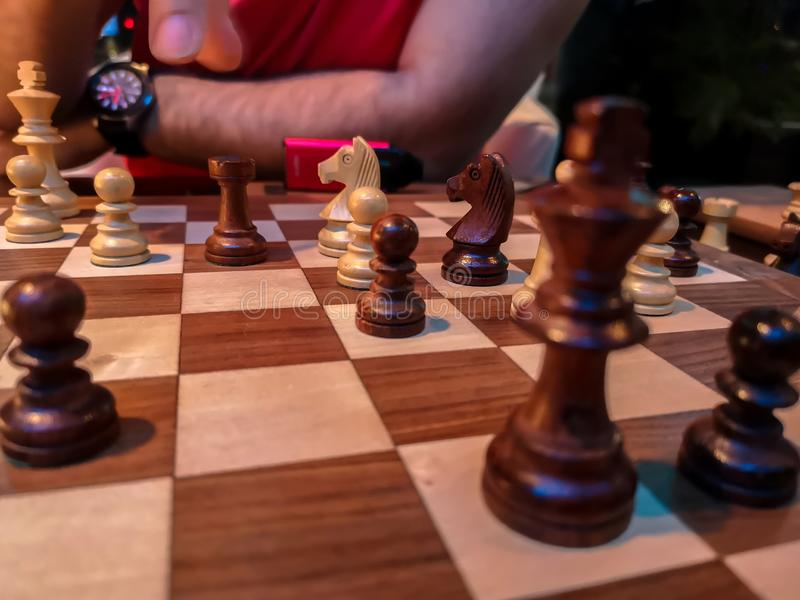 Män som spelar schack - konung och schackstycken på ett träbräde royaltyfri bild