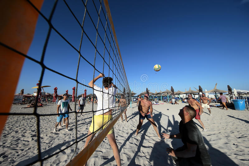 Män som spelar volleyboll på stranden royaltyfria foton