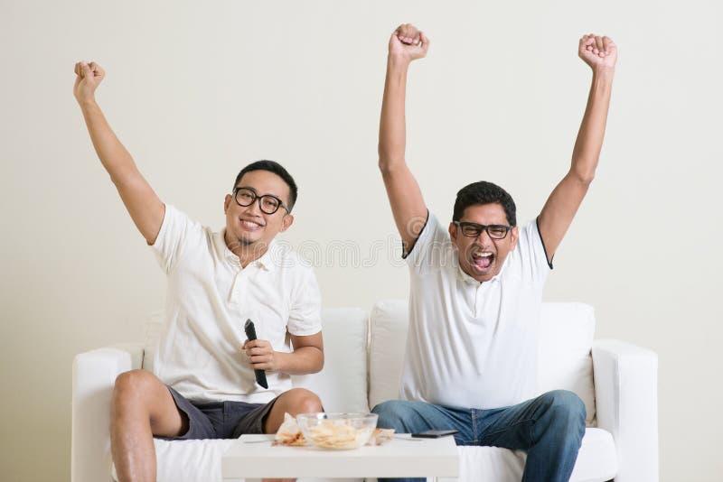 Män som tillsammans håller ögonen på fotbollleken royaltyfri foto