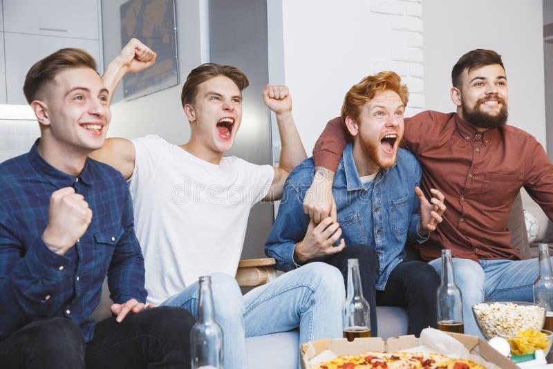 Män som tillsammans håller ögonen på sporten på att skrika för tv som hemma är gladlynt fotografering för bildbyråer