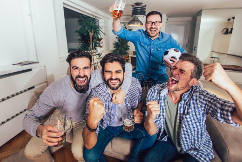 Män som tillsammans håller ögonen på sporten på att skrika för tv som hemma är gladlynt royaltyfria bilder