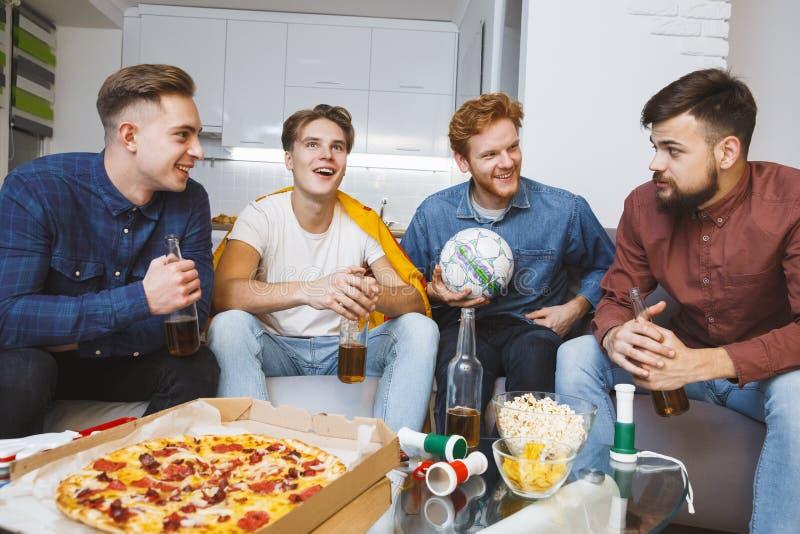 Män som tillsammans håller ögonen på sporten på den hemmastadda diskuterande leken för tv royaltyfria foton