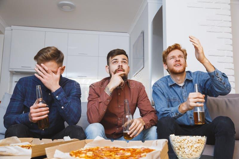 Män som tillsammans håller ögonen på sporten på hemmastadd förlust för tv arkivfoto