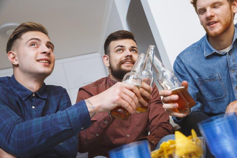 Män som tillsammans håller ögonen på sporten på hemmastatt rostat bröd för tv för lagnärbild royaltyfria bilder