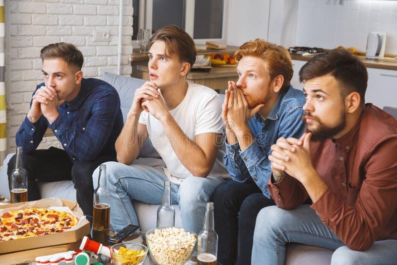 Män som tillsammans håller ögonen på sporten på nervös tv hemma royaltyfria bilder