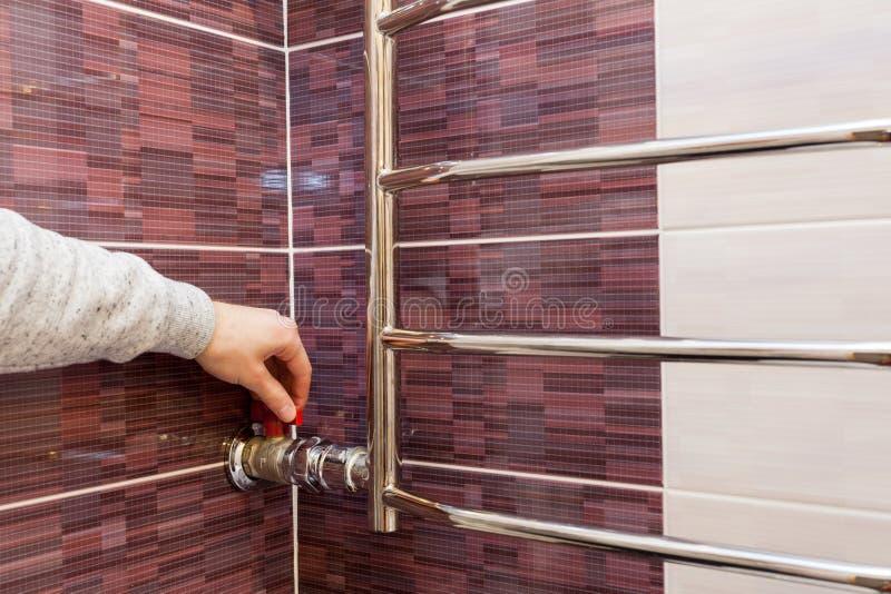 Männens hand reglerar vattenklappet i den upphettade handdukstången royaltyfri fotografi