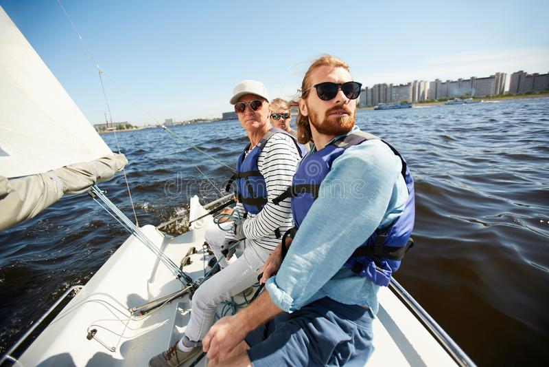 Männer in den Schwimmwesten, die auf Yacht sitzen lizenzfreie stockfotografie