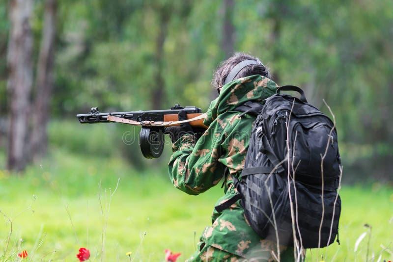 Männer in der Militäruniform mit Waffe stockfotografie