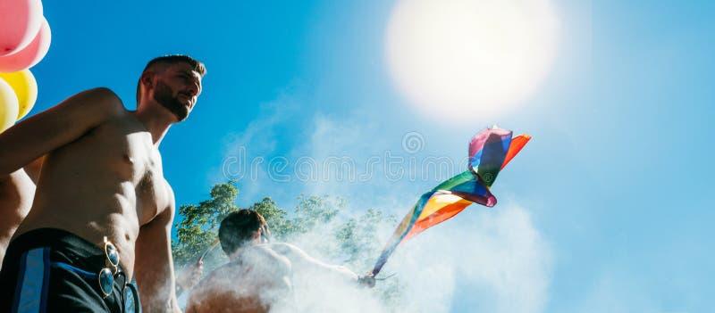 Männer des homosexuellen Stolzes, die LGBT-Leute auf LKW mit Regenbogenflagge tanzen stockbild