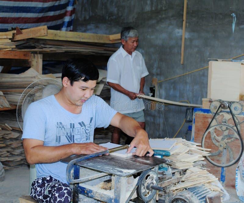 Männer, die an der Möbelfabrik in Saigon, Vietnam arbeiten stockbild
