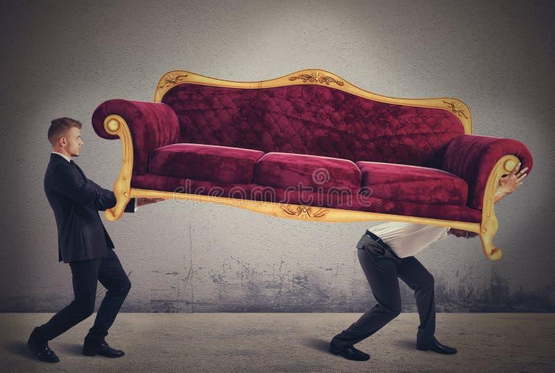 Männer, die ein Sofa tragen lizenzfreies stockfoto