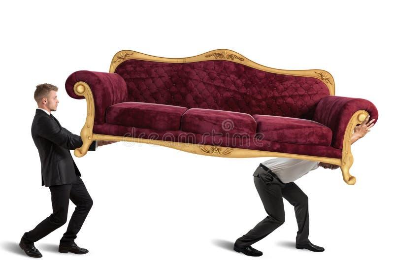 Männer, die ein Sofa tragen stockfotografie
