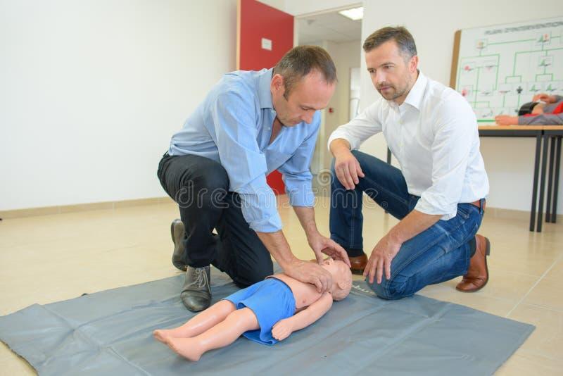 Männer, die erste Hilfe auf Kind sortierter Attrappe durchführen lizenzfreie stockfotos
