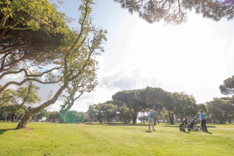 Männer, die Golf an sonnigem Tag Màlagas spielen lizenzfreie stockbilder