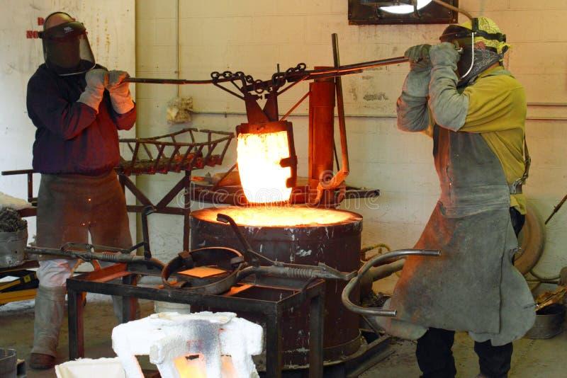 Männer, die im Gießerei-heißen Ofen arbeiten stockbild