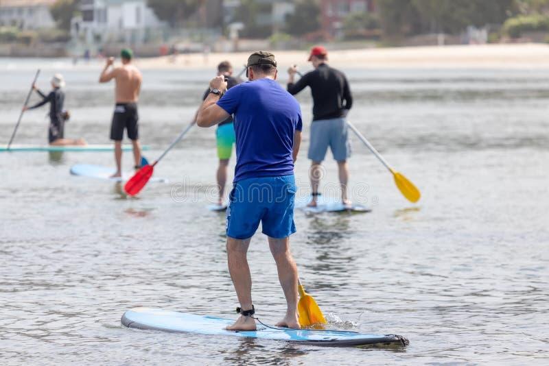 Männer, die im Ozean schaufeln lizenzfreie stockbilder