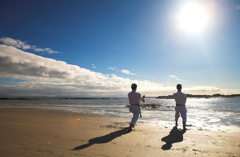 Männer, die Karate auf Strand üben lizenzfreie stockfotos