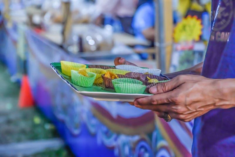 Männer, die Nahrungsmittelproben für das Schmecken im Nachtmarkt bei Thailand tragen lizenzfreie stockfotografie
