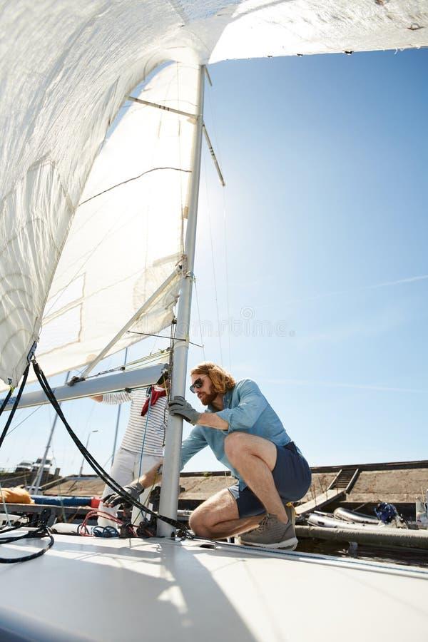 Männer, die Seile auf Segelboot binden lizenzfreies stockbild