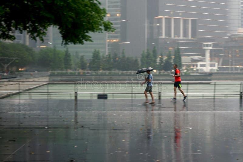 Männer, die unter dem Regen in Singapur rütteln stockfoto