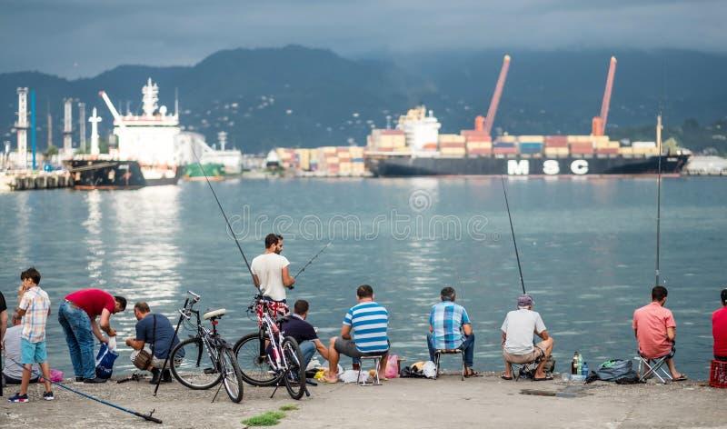 Männer, die von der Küstenpromenade fischen stockfotografie