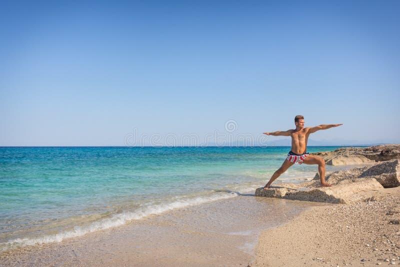 Männer, die Yoga auf dem Strand in Griechenland, in Position wa üben stockfotos