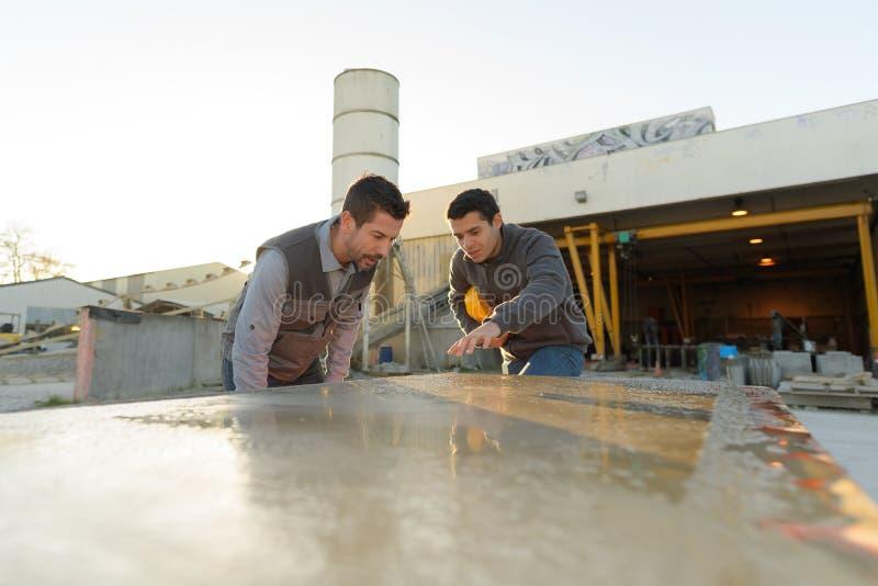 2 Männer entsteinen Ausschnittfabrik Stück Marmor-otudoors überprüfend lizenzfreie stockfotografie