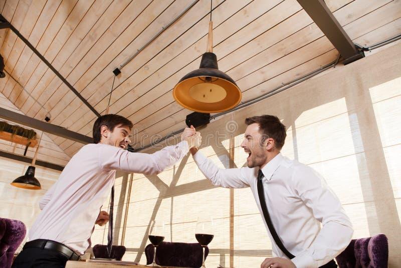 Männer lachen zusammen beim Treffen im Café lizenzfreies stockbild