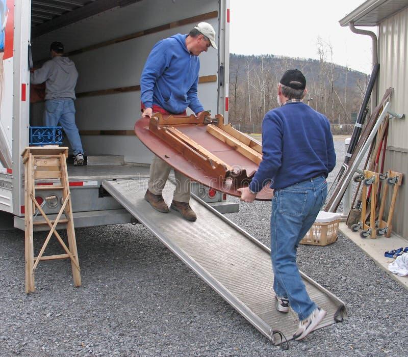 Männer laden einen beweglichen Packwagen lizenzfreie stockfotografie
