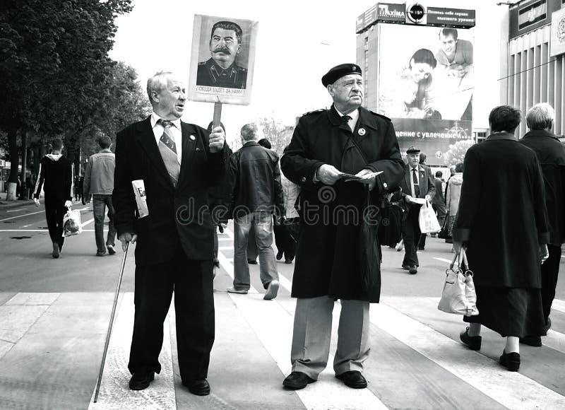 Männer am Maifeiertagsmarsch, der Porträts hält lizenzfreie stockfotografie