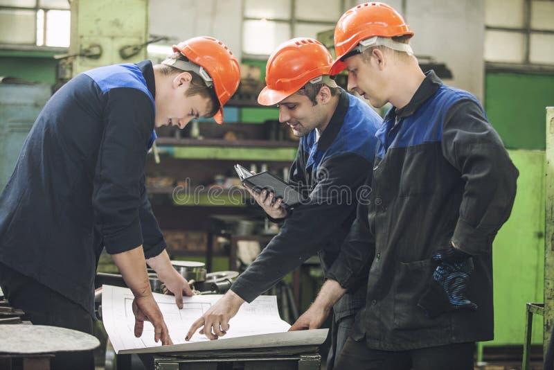 Männer mit den Zeichnungen, die in einer alten Fabrik arbeiten, um das Ausrüstung zu installieren stockbilder