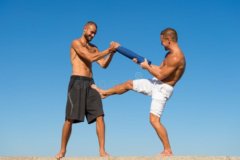 Männer mit der Yogamatte gefangen genommen im Hintergrund des blauen Himmels der Bewegung Sportlerkämpfen Kämpfende Fähigkeiten d lizenzfreie stockbilder