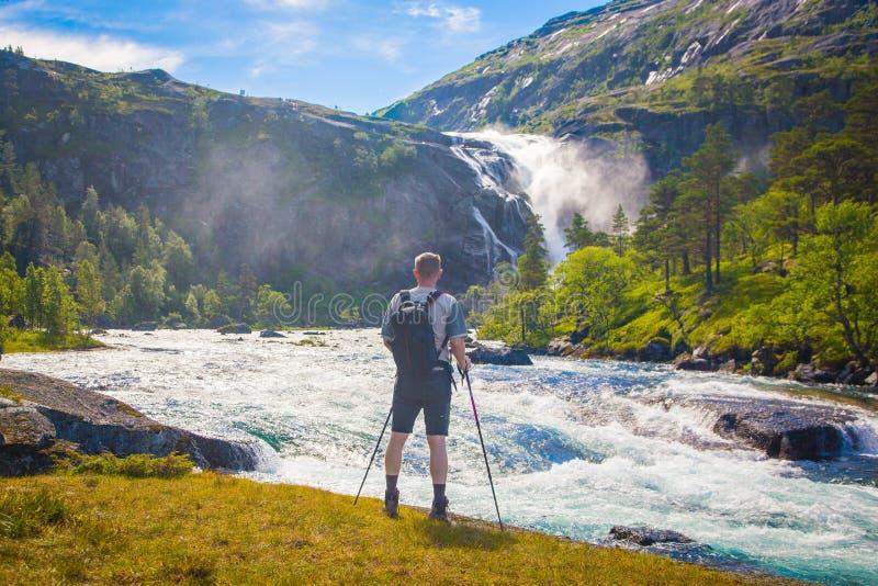 Männer mit einem Rucksack den Wasserfall, Norwegen aufpassend lizenzfreie stockbilder