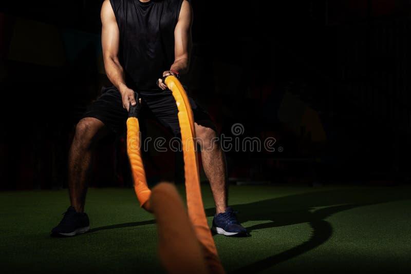 Männer mit Kampf fangen Funktionstrainingseignungsturnhalle, die Eignungsleute ein, die mit Kampfseilen an der Turnhalle trainier lizenzfreies stockbild