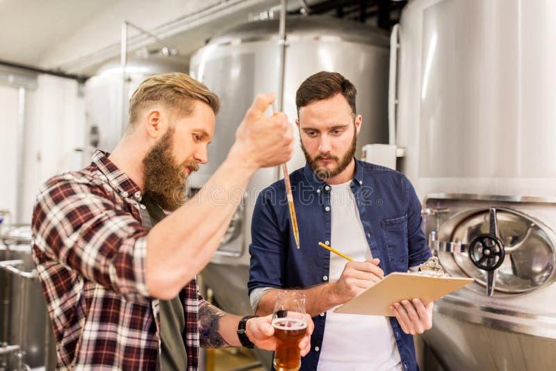 Männer mit Pipettenprüfungs-Handwerksbier an der Brauerei lizenzfreie stockfotografie